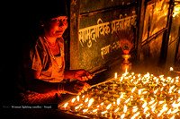 Old lady lighting candles at night in Boudhanath
