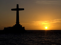 Christian Cross in the sea at sunset