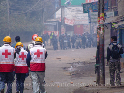 Red cross workers struggle with tear gas during riots in Kathmandu
