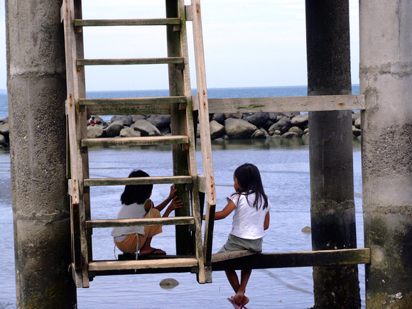 Two young girls play on a broken down watch tower along the shore in Davao City