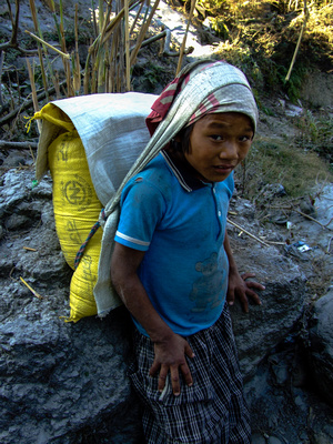 A small boy carrying a heavy load in the river mine
