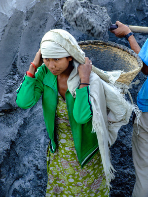 Young woman having sand loaded onto her back at the river mine in Nepal
