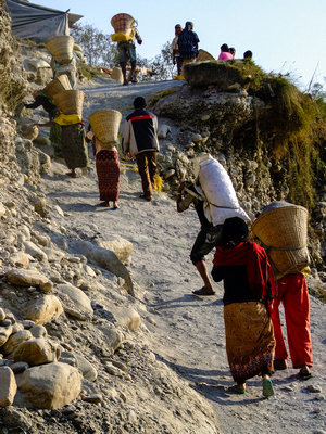Workers carrying heavy loads from a river mine in Nepal