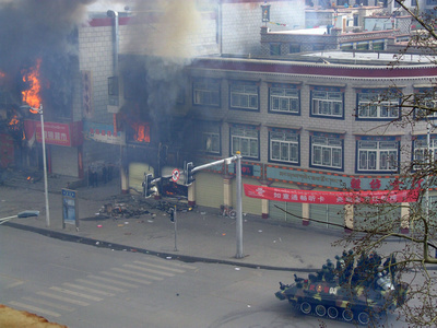 People sheltering during the riots in Tibet as a tank closes in