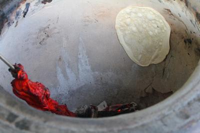 Tandoori Chicken and naan bread cooking in a tandoor