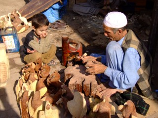 Father and son craving wood in Pakistan